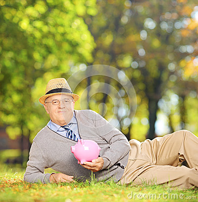Satisfied mature gentleman in a park holding a piggy bank