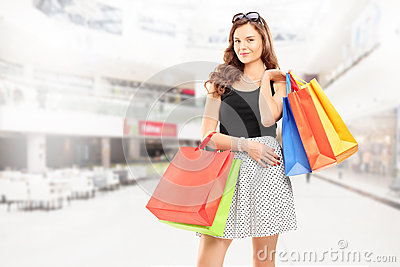 Satisfied young woman posing with shopping bags in a mall