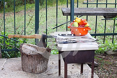 Saucepan with peppers and an ax in a wooden deck