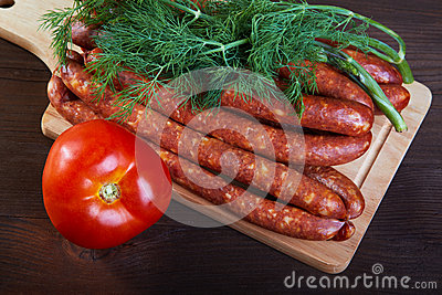 Sausage fennel and a tomato on an  wooden table