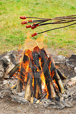 Sausages on sticks grilled above fire