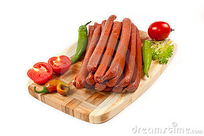 Sausages with a tomato and pepper on cutting board
