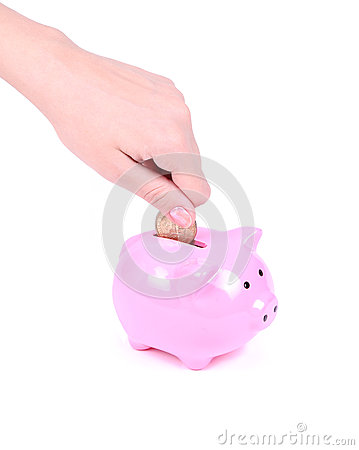 Saving money, hand is putting coin into piggy bank