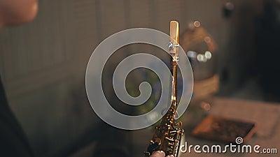 Saxofonista no revestimento que senta-se na cadeira que guarda o saxofone dourado jazz elegance video estoque