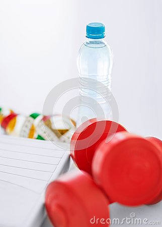 Scales, dumbbells, bottle of water, measuring tape