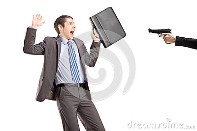 Scared businessman from a hand holding a gun