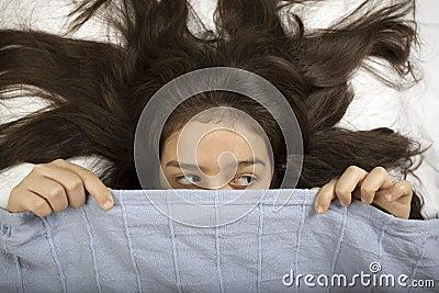 Scared girl hiding in bed