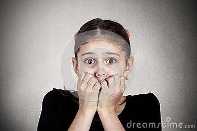 Young little girl biting her finger nails looking at you with fear