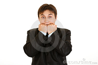 Scared young businessman holding hands near mouth