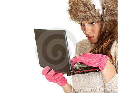 Scared young winter woman using laptop