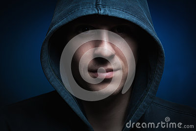 Scary man with hood in darkness