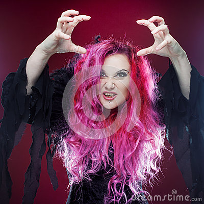 Free Scary Witch With Red Hair Performs Magic On A Pink Background. Halloween, Horror Theme. Royalty Free Stock Images - 74349749