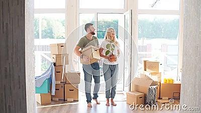 Scatole di cartone di trasporto delle coppie felici nella nuova casa il giorno commovente stock footage