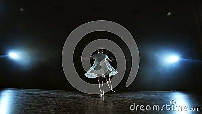 Scene dinamiche della performance musicale solitaria di una ballerina moderna Ballare sul palco sotto i riflettori in slow motion stock footage