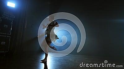 Scene dinamiche della performance musicale solitaria di una ballerina moderna Ballare sul palco sotto i riflettori in slow motion video d archivio