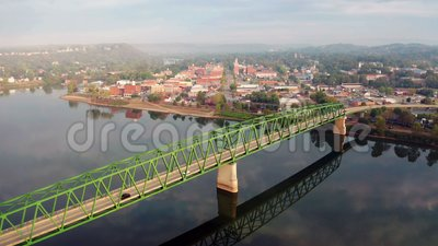 A scenic byway feeds tourists into the downtown area in the settlement called Marietta in Ohio State. Low hanging fog sticks around behind downtown and the stock video footage