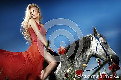 sch ne blondine die auf einem pferd im roten kleid sitzen. Black Bedroom Furniture Sets. Home Design Ideas