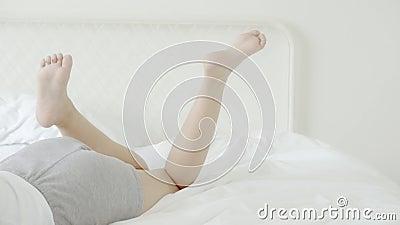 Schöne Frauenbeine schließen, die sich im Schlafzimmer auf das Bett bewegen, Mädchen zeigen Füße attraktiv liegen Bett stock footage