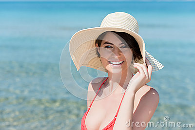 Schöne junge Frau, die auf einem Strand aufwirft