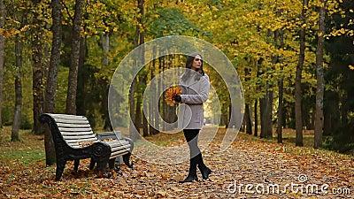Schöne junge Frauen, die um gehen und auf der Bank im Park im Herbst, auf jemand wartend sitzen stock video