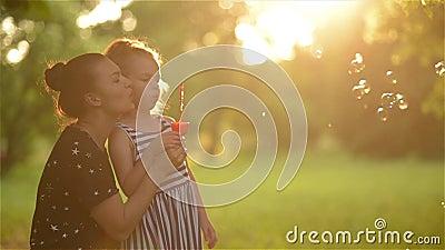 Schöne Mutter mit ihrer Tochter in der Natur, die Seifenblasen und das Lachen macht