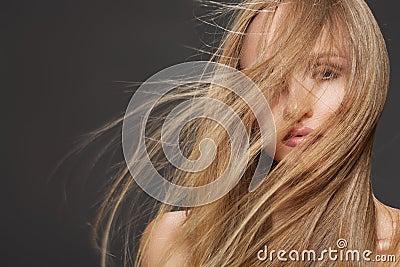 Schöne vorbildliche Frau, die Kopf mit dem langen Haar rüttelt