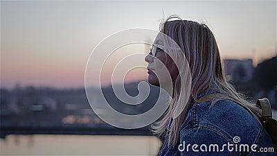 Schöner roter Sonnenuntergang über dem Fluss Das Mädchen sitzt auf der Ufergegend und den Blicken in den Abstand Sch?ner Film- Ra stock footage