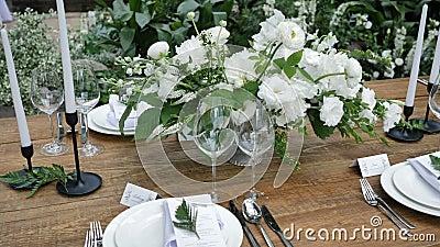 Schönes Dekor eines alten Holztisches für einen Hochzeitsabend im rustikalen Stil mit Blumenstraukeln und Kerzen stock video