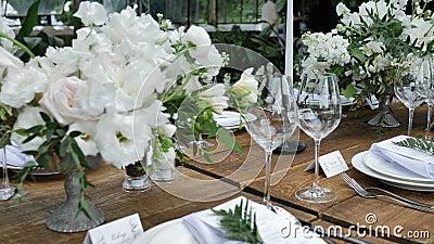 Schönes Holztisch-Dekor für ein Hochzeitsessen im rustikalen Stil mit Blumenmotiven und Kerzen stock video