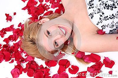 Schönes jugendlich Mädchen, das auf Rosen-Blumenblatt über Weiß legt