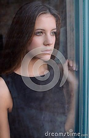 Schönes jugendlich Schauen durch Fenster
