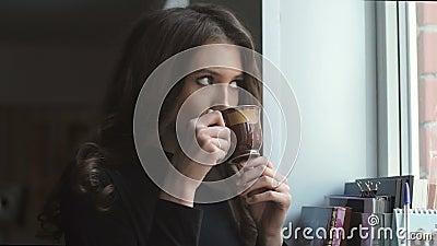 Schönes junges Mädchen, das nahe bei dem Fenster und dem trinkenden coffe steht stock footage
