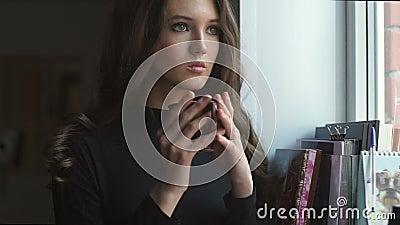 Schönes junges Mädchen, das nahe bei dem Fenster und dem trinkenden coffe steht stock video footage
