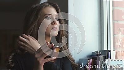 Schönes junges Mädchen schaut durch das Fenster und trinkt coffe stock video