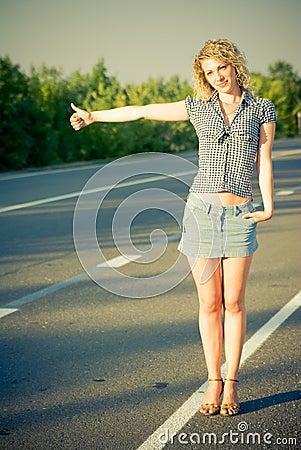 Schönes Mädchen, das auf der Straße trampt