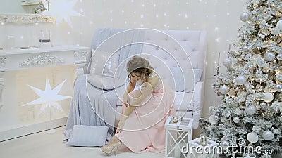 schönes Mädchen trinkt Champagner und sitzt auf dem Sofa im Dekor des neuen Jahres stock footage