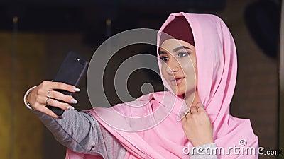Schönes Muschelmädchen in Hijab, das sich selbst macht, mit Handy-Kamera Muslime und moderne Technologie stock video