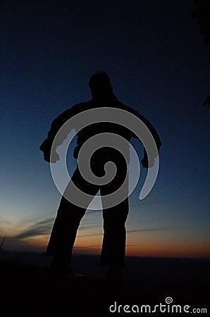 Schattenbild des Mannes am Sonnenuntergang