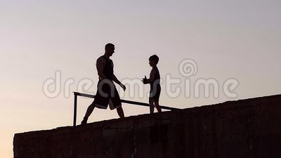 Schattenbild des Vaters And Son Standing auf Pier And Engaged In Sports stock video footage