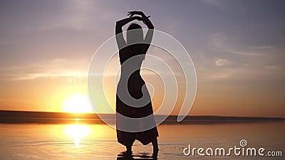 Schattenbild eines schlanken Mädchens, das auf das Wasser in den Yogahosen, Erhöhungen ihre Hände geht Sorglos, Freiheit Unglaubl stock footage