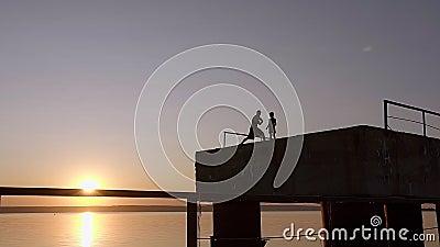 Schattenbild von Sportlern bringen And Son On Pier In The Evening hervor stock video