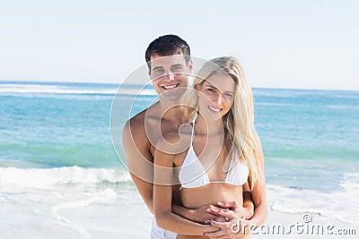 Schitterend paar die en bij camera omhelzen glimlachen