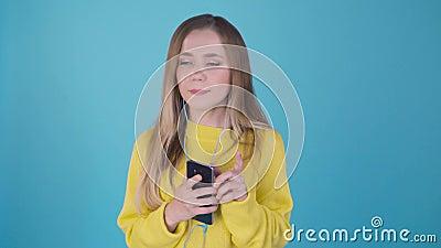 Schitterende blondy dame in gele sweater het luisteren muziek in hoofdtelefoons en het zingen op blauwe achtergrond Charmant meis stock footage