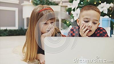 Schließen Sie 4k Video von erstaunlichen Geschwistern kaufen Weihnachtsgeschenke online mit Laptop zusammen stock video