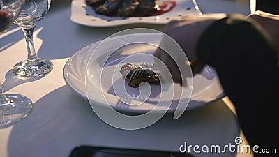 Schließen Sie oben von Frau ` s Händen, die Fische und Hieb auf einer Platte im Restaurant 4K schneiden stock footage