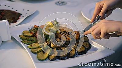 Schließen Sie oben von Frau ` s Händen, die Fische und Hieb auf einer Platte im Restaurant 4K schneiden stock video