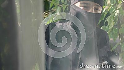 Schließung des Diebstahls in schwarzen Kleidung und Balaclava in das Fenster schauend, um in das Haus zu brechen Vorbereitung auf stock video footage