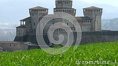 Schloss von Torrechiara in Parma, Italien durch windiges Wiesengraspanorama - vertikales Verschieben Emilia Romagna-Region stock video