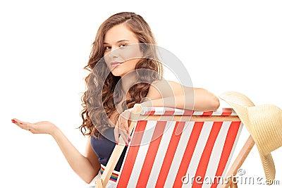 Schöne junge Frau, die auf einem Sonnenruhesessel sitzt und Esprit gestikuliert