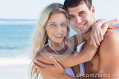 Schöne Paare, die an der Kamera umarmen und lächeln